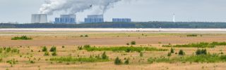 Steaming cooling towers of the Jänschwalde lignite-fired power plant can be seen behind a large field.