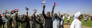 Supporters of President Omar al Bashir wave Sudanese flags during a rally for him at the Green Square in the capital Khartoum on Jan. 9, 2019.
