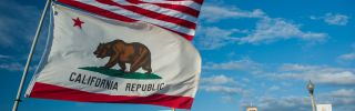 The flags of the United States and America and the state of California flap against an azure sky.