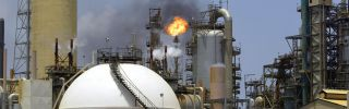 A controlled flame burns behind a storage tank at an oil refinery complex in Venezuela.