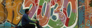 A man rides past graffiti alluding to Vision 2030