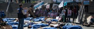 """Extinction Rebellion and Planete Amazone activists stage a """"die-in"""" on May 14, 2019, in front of the Grande Arche de La Defense in Puteaux, northwest of Paris."""