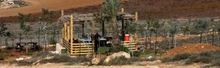 Settlers sit in a shack north of the Palestinian village of al-Mughayyir near the Israeli settlement of Shilo in the occupied West Bank on Nov. 20, 2018.