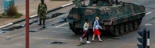 Two young women walk past an armored personnel carrier in Zimbabwe's capital, Harare, under the watch of soldiers regulating traffic.