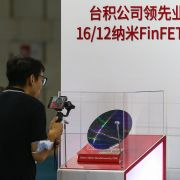 A visitor takes photos at the 2020 World Semiconductor Conference on Aug. 26, 2020, in Nanjing in China's eastern Jiangsu province of a chip made by Taiwan Semiconductor Manufacturing Co.