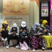 Women sit along the side of a street in Hong Kong on Jan. 28. They're each wearing sanitary masks to protect themselves from the coronavirus.