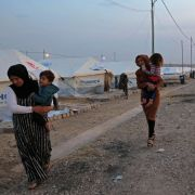 Syrian refugees walk outside a tent at a camp near the Iraqi Kurdish town of Bardarash on Oct. 18, 2019.