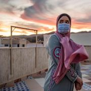 A woman wearing a face mask stands at a terrace on top of a building in Fnideq, Morocco, on Aug. 28, 2020.