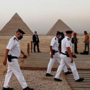 Policemen walk near an overlook at the Giza Pyramids in Egypt ahead of a ceremony commemorating the launch of the site's first environmentally-friendly bus and restaurant on Oct. 20, 2020.
