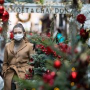 A pedestrian wearing a face mask walks past Christmas-themed window displays inside Burlington Arcade in London, the United Kingdom, on Nov. 23, 2020.