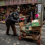 A woman pushes a cart down a street in Beijing, China, on March 5, 2021.