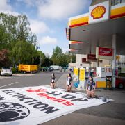 Environmental activists covered in black paint take part in a demonstration at a Shell gas station in The Hague, Netherlands, on May 18, 2021.