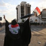 A woman waves an Iraqi flag as riot police charge toward protesters in Baghdad on May 25, 2021.
