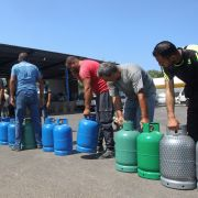 People wait to fill up fuel tanks in the southern Lebanese city of Sidon on Aug. 10, 2021.