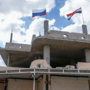 Russian and Syrian flags wave above a damaged building in Syria's southern city of Daraa on Sept. 12, 2021.