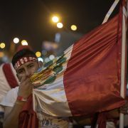 A supporter of ousted Peruvian President Martin Vizcarra embraces the country's national flag during a protest in Lima, Peru, on Nov. 14, 2020.