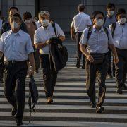 People wearing face masks cross a street on July 28, 2021, in Tokyo, Japan.