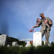 A soldier places flags at the gravesites of U.S. military members buried at the Arlington National Cemetery in Virginia on May 24, 2012.