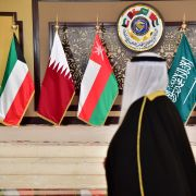 A man walks past the flags of the countries attending the Gulf Cooperation Council (GCC) summit in Kuwait City, Kuwait, on Dec. 5, 2017.