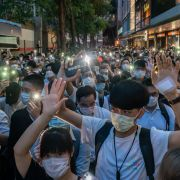 Pro-democracy protesters shine the flashlights on their cellphones as they take part in a rally in Hong Kong on June 9, 2020.