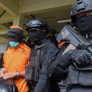 Police escort one of 19 terror suspects being transferred to Jakarta fro Makassar on Feb. 4, 2021, at Sultan Hasanuddin International Airport in Makassar, Indonesia.