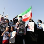 Supporters of Iranian presidential candidate Ebrahim Raisi hold campaign posters at a rally in Tehran on June 14, 2021.