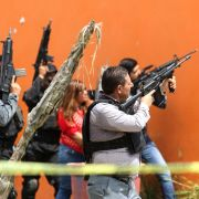 Mexican police take position outside a house during a search in Tlajomulco de Zuniga, Jalisco State, Mexico, on June 21, 2019.