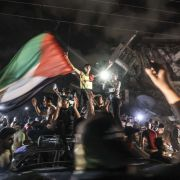 People in Gaza City wave the Palestinian flag in celebration of the cease-fire reached between Israel and Hamas on May 21, 2021.