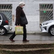 A woman wearing a protective mask carries a grocery bag in Dedovsk, Russia, on April 16, 2020. To contain the COVID-19 outbreak, Russian President Vladimir Putin recently extended the government's national stay-at-home order until May.