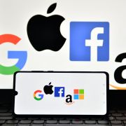 A picture taken in London on Dec. 18, 2020, shows the logos of Google, Apple, Facebook, Amazon and Microsoft displayed on a mobile phone and laptop screen.