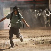 A man wearing a gas mask runs from a clash with police in Santiago, Chile, during a protest on Dec. 10, 2019.