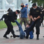 Plainclothed Belarus' security forces and riot police officers detain a protester at an opposition demonstration in Minsk, Belarus, on July 14, 2020.