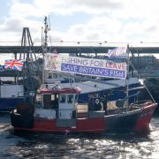 Fishing boats waving pro-Brexit flags sail up the River Tyne on March 15, 2019, in North Shields, United Kingdom.