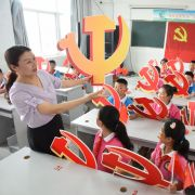 A teacher and her students hold Chinese Communist Party emblems during a lesson about the party's history in Lianyungang, China, on June 28, 2020.