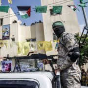 A masked Hamas militant mans a machine gun in the back of a pickup truck in the Palestinian city of Rafah, located in the southern Gaza Strip, on Oct. 17, 2019. The yellow flags of the Palestinian party Fatah can also be seen in the background.