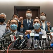 Pro-democracy lawmakers join hands during a press conference at Hong Kong's Legislative Council after city officials ousted four of their colleagues on Nov. 11, 2020