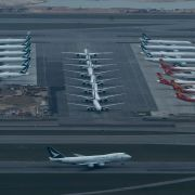 A Cathay Pacific aircraft takes off on a runway as others park at Hong Kong International Airport on March 6, 2020.