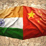 An image depicts waving Chinese and Indian flags overlaying a map of the world.