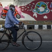 A man wearing a bandana peddles his bicycle in front of a mural depicting the globe covered in a mask on April 13, 2020, in New Delhi, India.