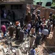 Kashmiri villagers gather around a partially damaged house after a gunfight in Pulwama, South of Srinagar, on May 18, 2019, after four rebels died in two separate clashes.