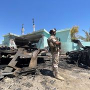 A member of the Iraqi security forces stands by a destroyed vehicle on July 8, 2021, after rockets landed on the Ain al-Asad airbase in Iraq's western Anbar province, which hosts U.S. troops.