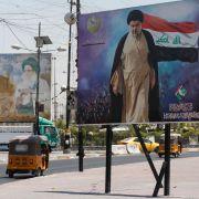 A tuk-tuk car drives past a large poster of Shiite cleric Moqtada al-Sadr, in al-Sadr City, Iraq, on July 15, 2021.
