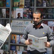 Men read local newspapers in Amman, Jordan, on April 4, 2021.