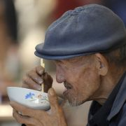 An elderly man tucks into some noodles on the street in Beijing.