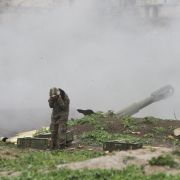 Armenian soldiers belonging to Nagorno-Karabakh's army fire an artillery shell toward Azerbaijani forces on April 3.