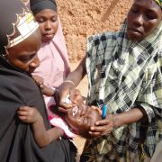 A health care worker administers an oral dose of polio vaccine to a child in northern Nigeria.