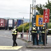 Police officers watch protesters rally against the Northern Ireland protocol in Belfast on July 3, 2021.