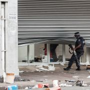 A police officer scans a looted retail store in central Durban, South Africa, on July 11, 2021.