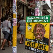 People in Johannesburg walk past an election poster promoting the African National Congress on April 28, 2019.