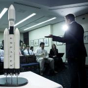 SpaceX CEO Elon Musk delivers a presentation while standing beside scale models of the rockets his company produces.